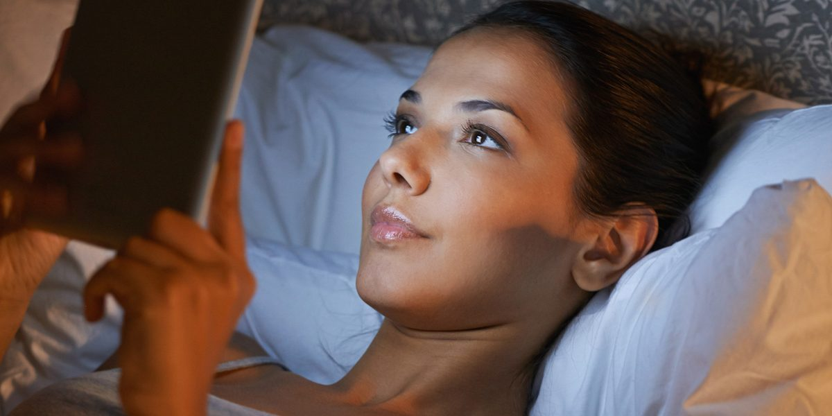Woman reading an iPad in bed