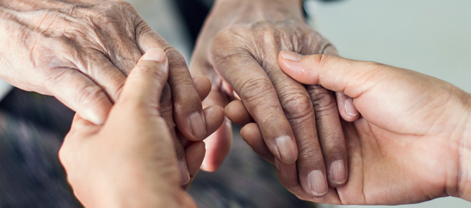 Caretaker holding an elderly person's hands