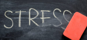 The word 'STRESS' on a chalkboard being wiped away by an eraser.