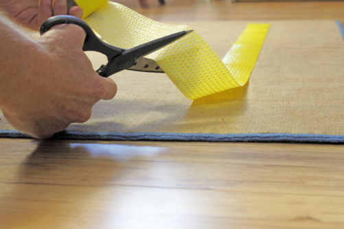 Man cutting and applying an anti-skid carpet tape on area rug.