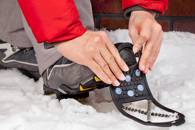 Man, kneeling in the snow, putting ice cleats on his hiking boots