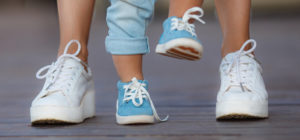 Close up of toddler's feet learning to walk, alongside Mom's feet