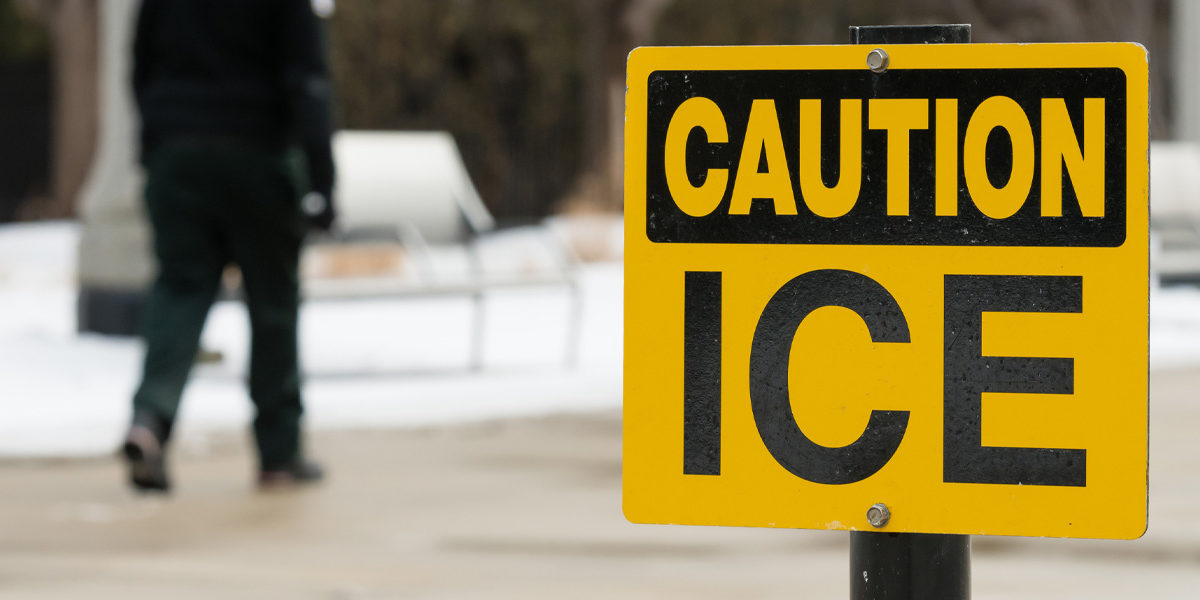 "Photo with ""CAUTION ICE"" sign and man walking on sidewalk in the distance"