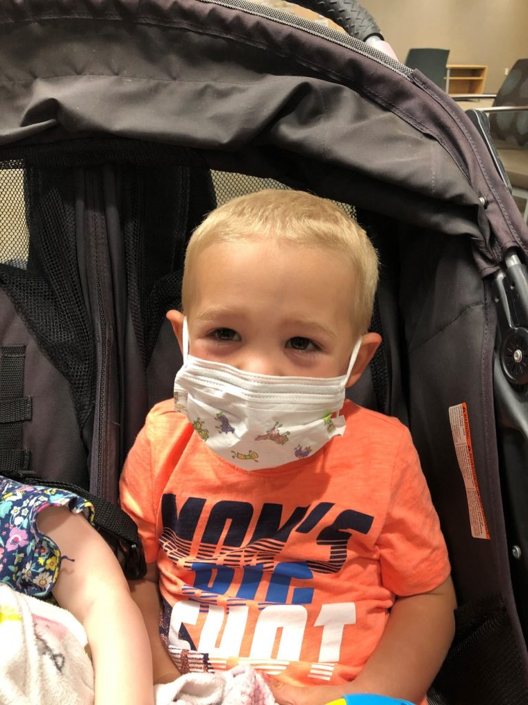 3-year-old boy with blonde hair wearing a surgical mask in a stroller