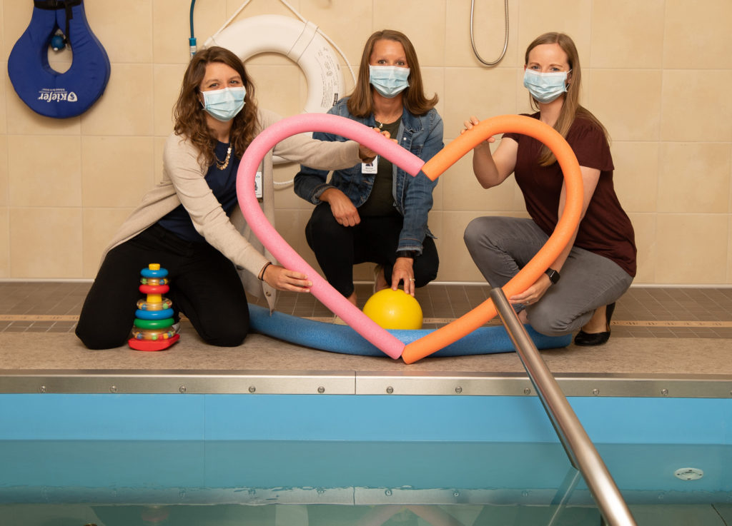 Pediatric therapists at the therapy pool with heart-shaped noodles