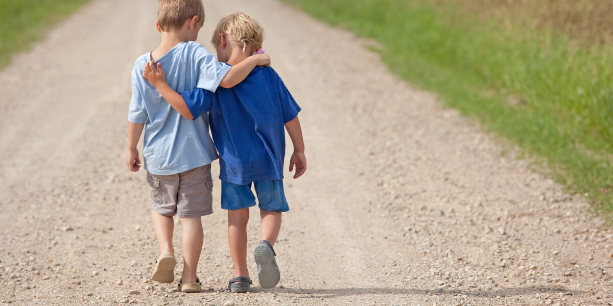 Two boys walking down a dirt road, arms around each others shoulders