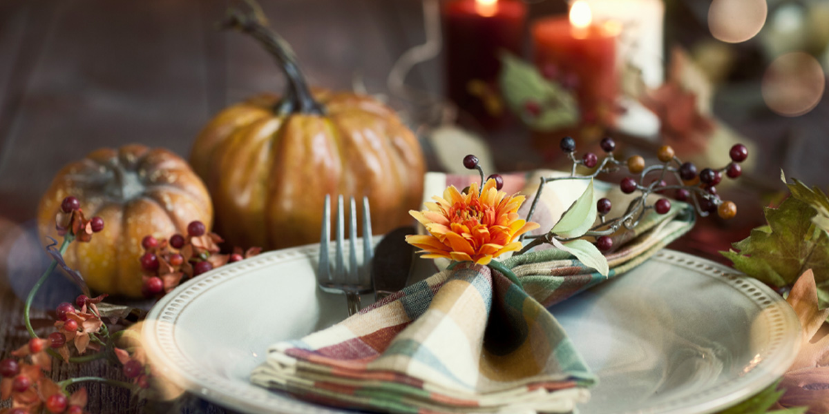 Autumn place setting with decorative pumpkins, candles and berries