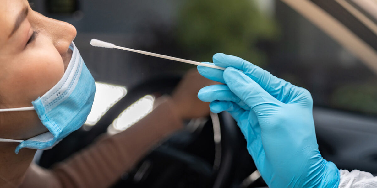 Woman in car getting tested for COVID-19 with nasal swab