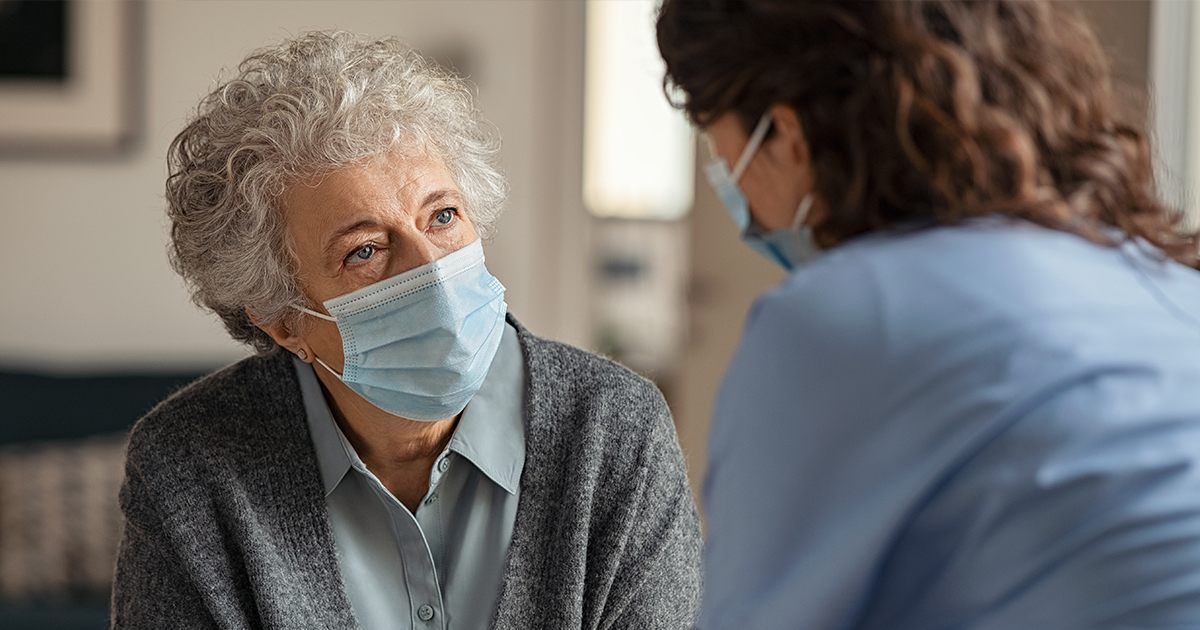 Older female patient talking to her healthcare provider, both wearing masks