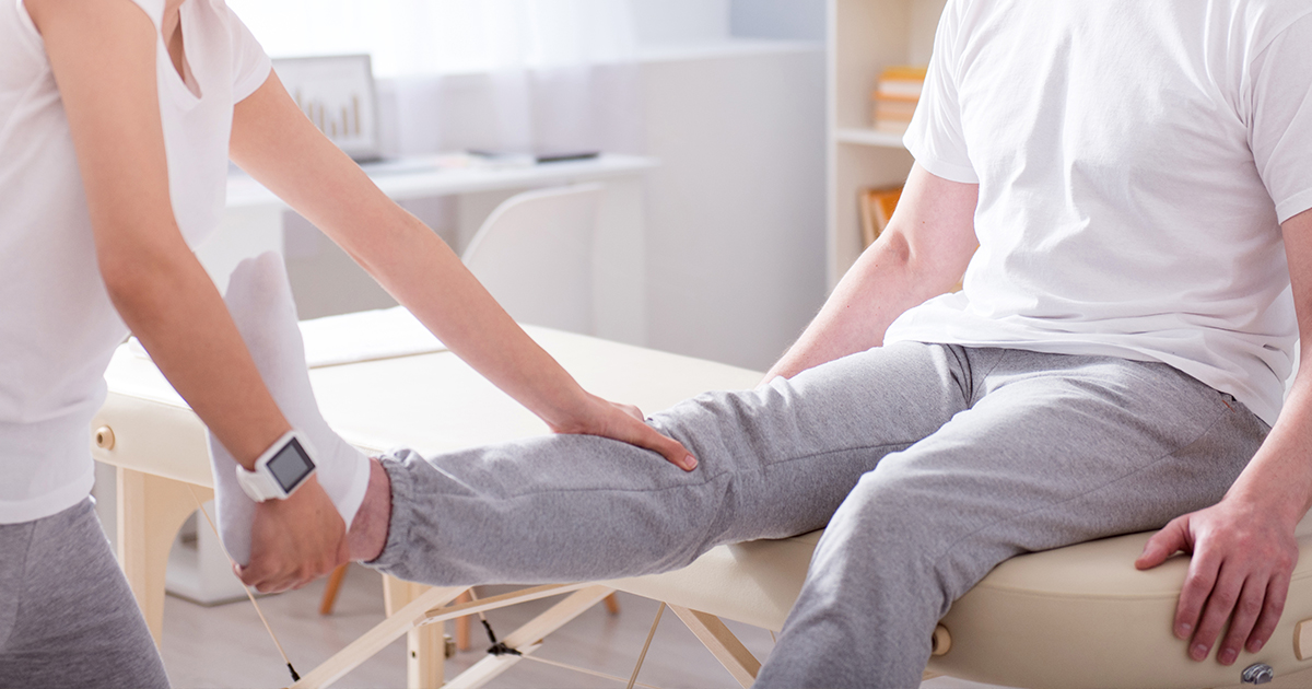 Female physical therapist assessing male patient's lower leg and knee