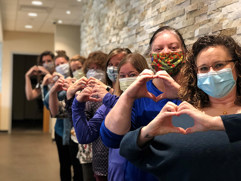 Welia Health registration staff posing with heart hands