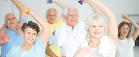 senior citizens raising dumbbells overhead in fitness class