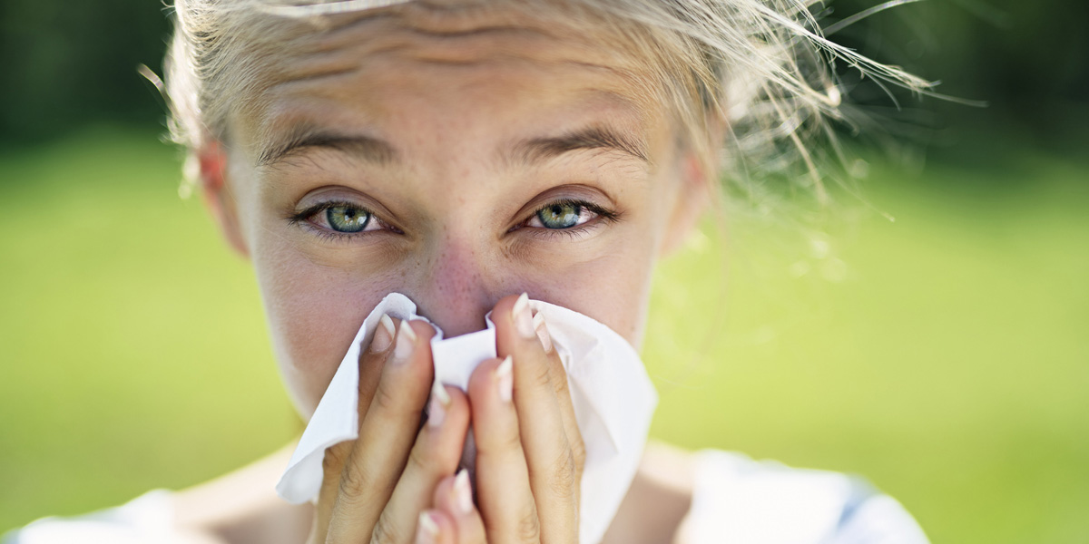 Teenager with allergies blowing her nose