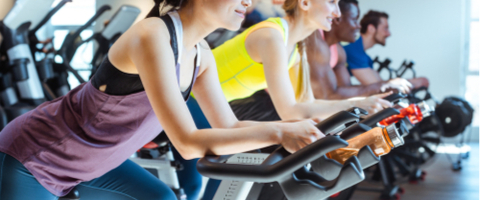 Men and women exercising on indoor spin bikes