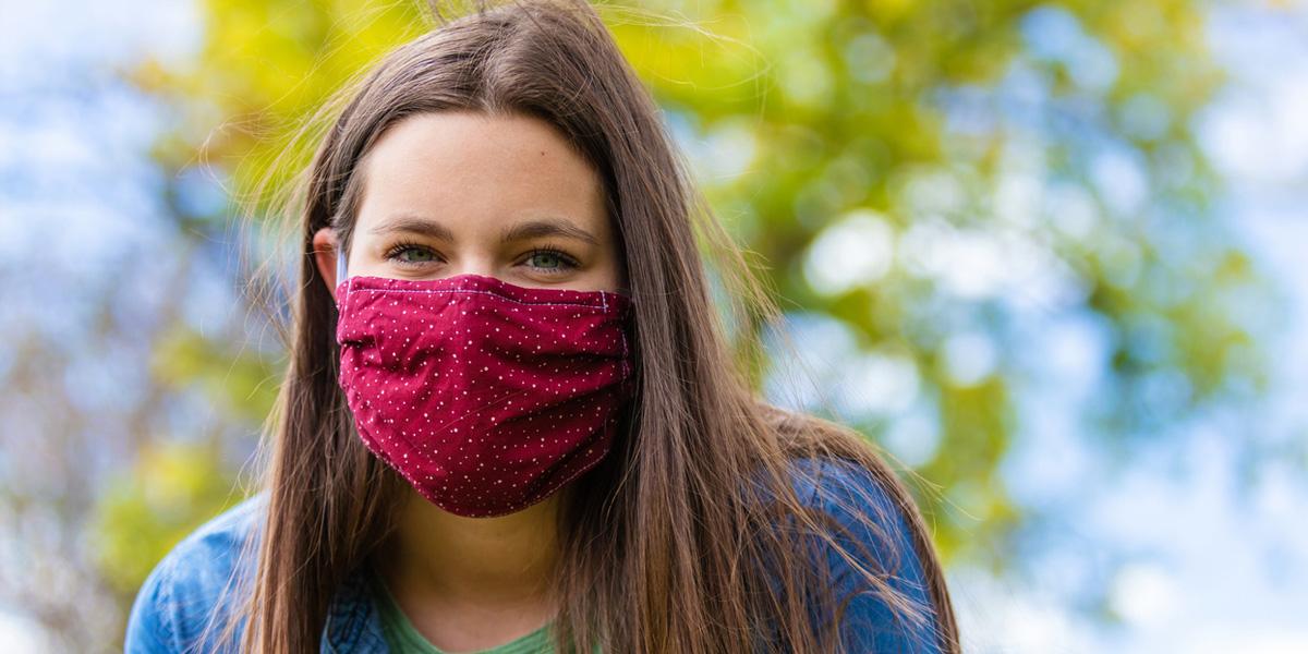 Young woman wearing a mask, sitting outside