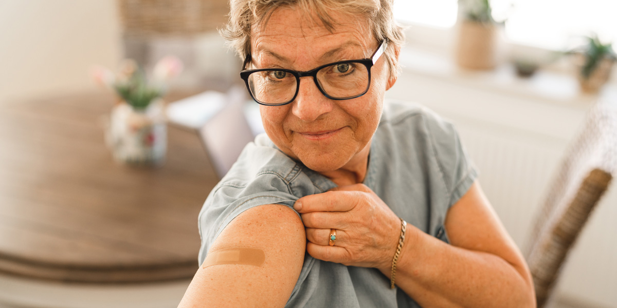 Older woman showing offer the band-aid from her COVID-19 vaccine