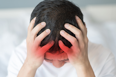 Young man holding his head with red hue near front indicating he has a concussion.