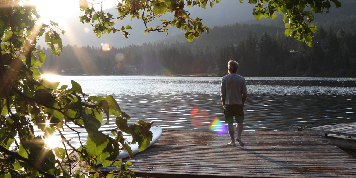 A man standing on a dock next to the lake