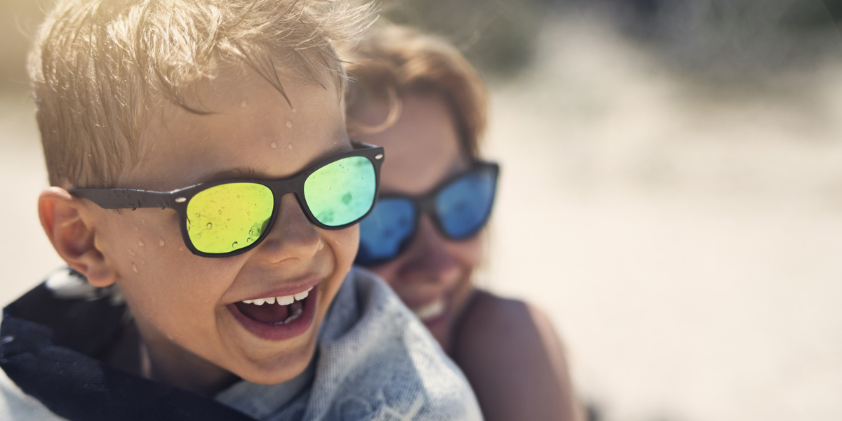 Mother and sun at the beach wearing sunglasses and laughing