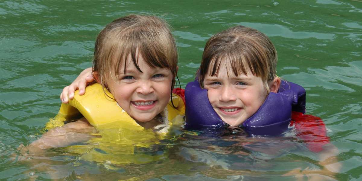 Two girls, with lifejackets, swimming in a lake